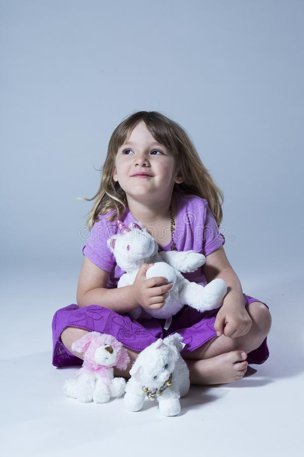 Foto vertical da menina bonito na saia superior e roxa malva que senta-se de pernas cruzadas fotos de stock royalty free