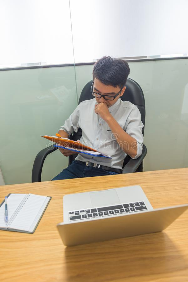 Foto vertical de dados financeiros de leitura do homem de negócios asiático no relatório fotografia de stock royalty free
