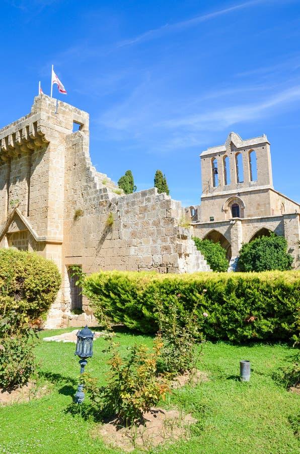 Foto vertical de la abadía medieval de Bellapais en Chipre septentrional turco Capturado con el parque adyacente y con el cielo a fotografía de archivo libre de regalías