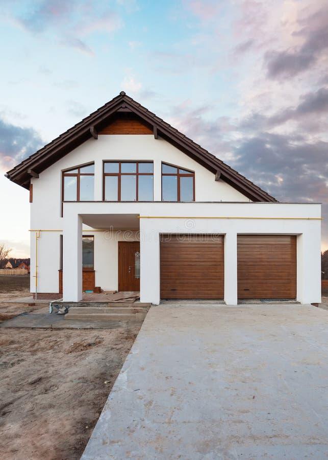 Foto vertical de la comodidad hermosa y de la nueva casa con las ventanas grandes del garaje del tejado marrón de la puerta y la  imagen de archivo