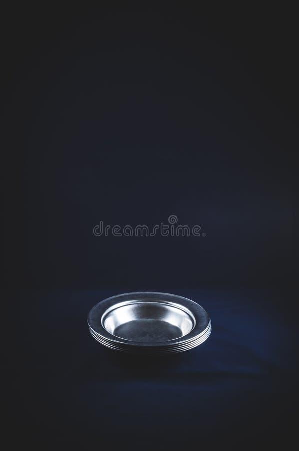Foto vertical de pratos de aço inoxidável do ferro em um fundo azul com um matiz agradável imagens de stock royalty free