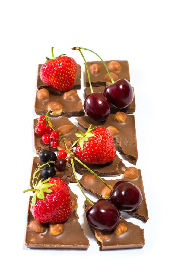 Foto vertical de ricos da barra de chocolate nas avelã com fruto diferente nele Isolado na perda de peso branca da tentação do fu foto de stock royalty free