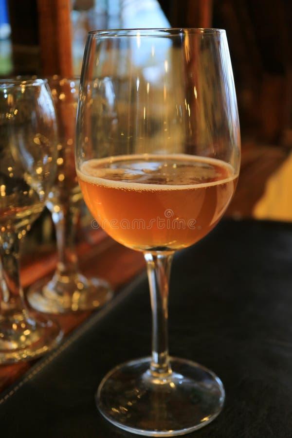 A foto vertical de um vidro da cor ambarina refrigerou a cerveja do ofício na mesa de jantar foto de stock