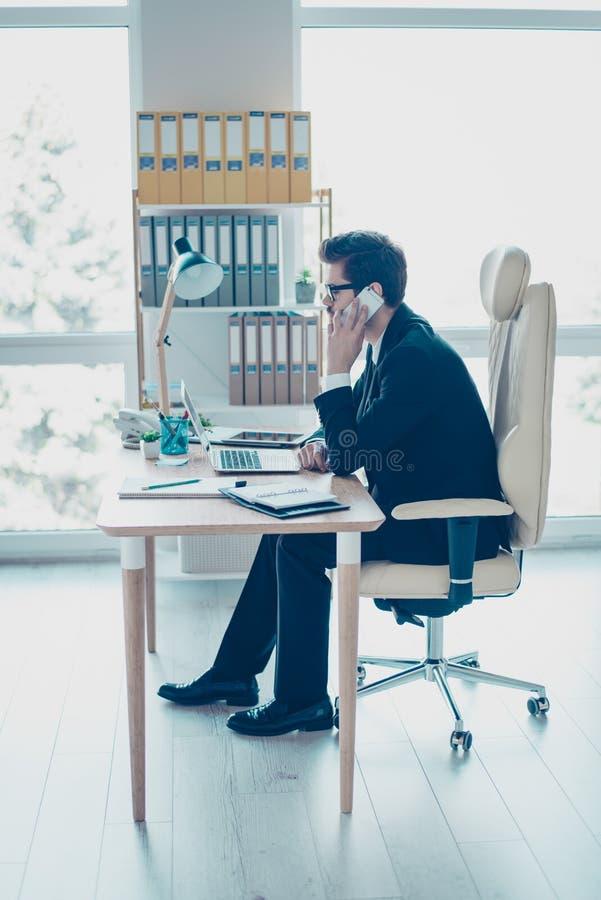 Foto vertical do empregador novo bem sucedido ocupado que fala no sma imagens de stock