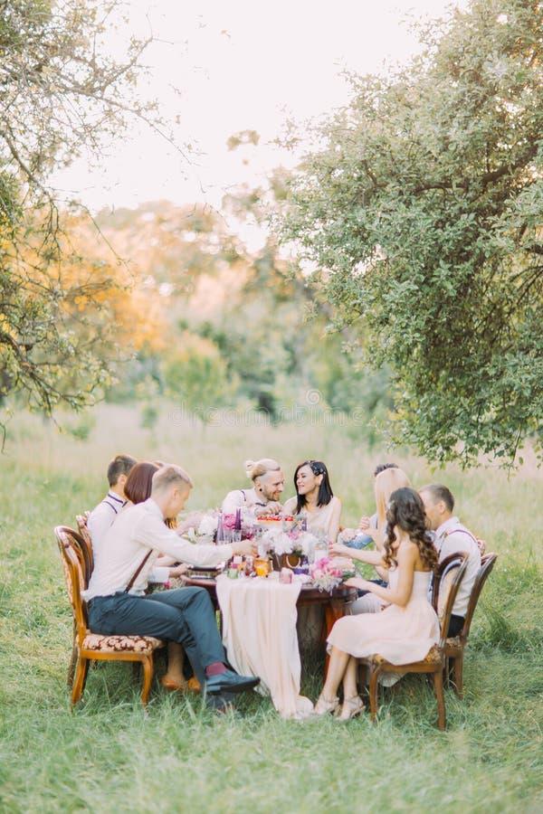 A foto vertical do jantar de casamento com os recém-casados e os convidados que comemoram o ceremeny na floresta ensolarada imagens de stock