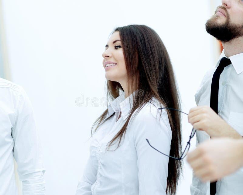 Foto verticale condizione sorridente della donna di affari vicino al deskto fotografia stock libera da diritti