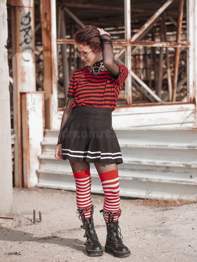 Foto verticale di una ragazza gotica alternativa su uno sfondo di costruzione abbandonato teenager emo immagini stock libere da diritti