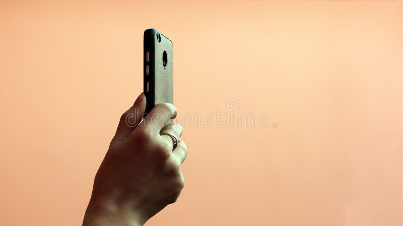 Foto of video die op een mobiele telefoon schieten De hand van een meisje met een gouden ring op haar vinger houdt een smartphone royalty-vrije stock afbeeldingen