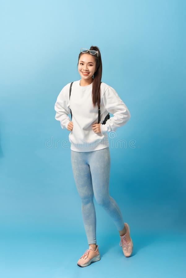 Foto in voller Länge der asiatischen Studentin, die mit dem Rucksack lokalisiert über hellblauem Hintergrund geht lizenzfreies stockfoto