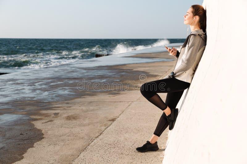 Foto in voller Länge der jungen hübscher Frau in Sportabnutzung listenin lizenzfreies stockbild