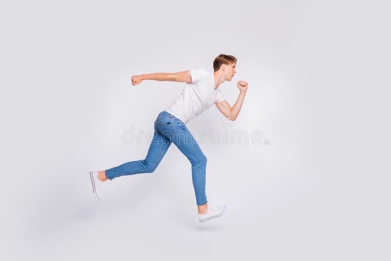 Foto in voller Länge des Springens des hohen Kerls bereit, Rennen anzufangen, weißen Hintergrund der zufälligen Ausstattung zu tr lizenzfreie stockbilder