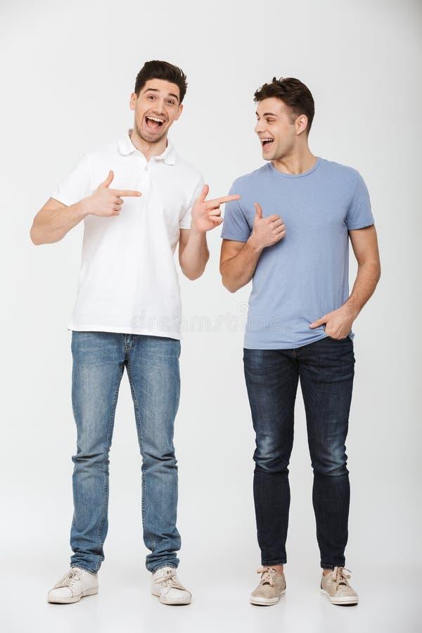 Foto in voller Länge von zwei gutaussehenden Männern 30s, die zufälliges T-Shirt tragen stockbilder