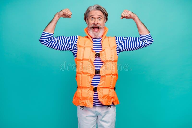 Foto von attraktiven lustigen alten Kerl gute Laune zeigen Biceps starke Marine Rettungsschwimmer Seereise tragen gestreiften See stockfoto