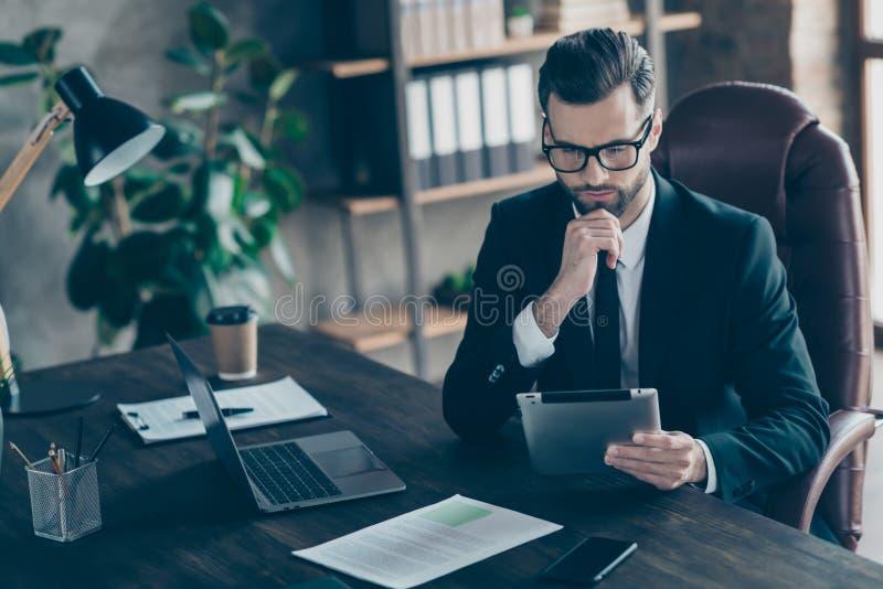 Foto von aufmerksamer, gut aussehender Geschäftsmann, der sich auf das Lesen von E-Reader-Berichten konzentriert, um die Zahlen d lizenzfreie stockfotos