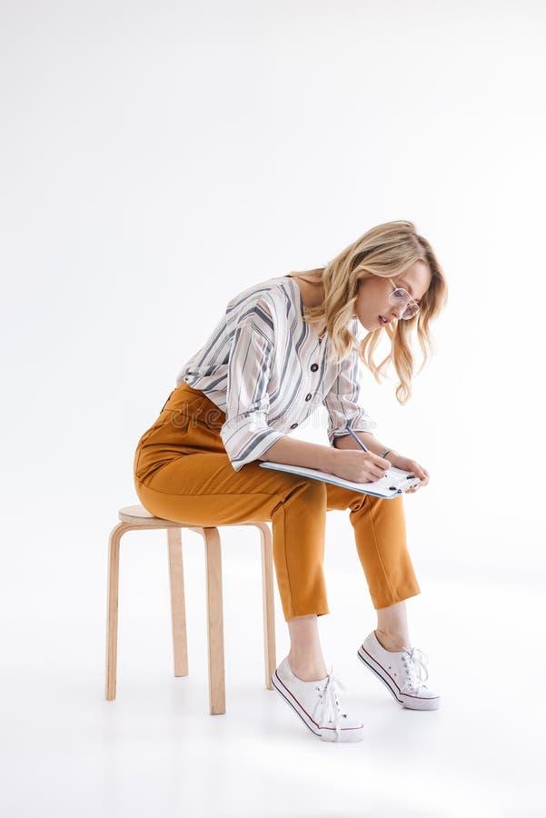 Foto von den europ?ischen denkenden tragenden Gl?sern der Frau, die im Stuhl sitzen und auf Klemmbrett schreiben lizenzfreie stockbilder