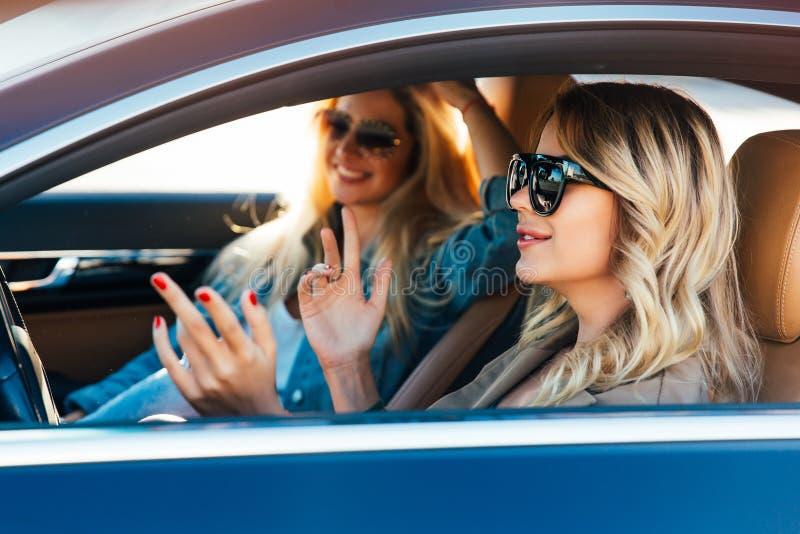 Foto von den glücklichen Blondinen, die Sonnenbrille beim Fahren in Auto tragen stockbilder