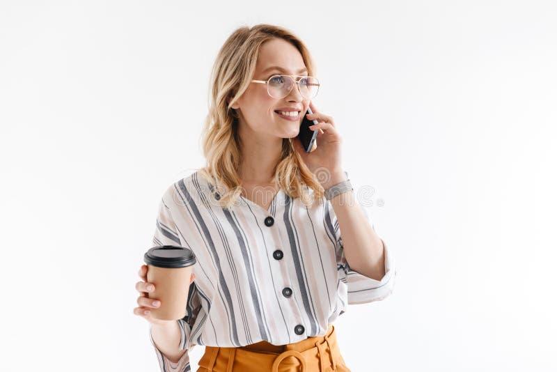 Foto von den l?chelnden tragenden Gl?sern der attraktiven Frau, die auf Mobiltelefon sprechen und Papierschale halten lizenzfreie stockbilder