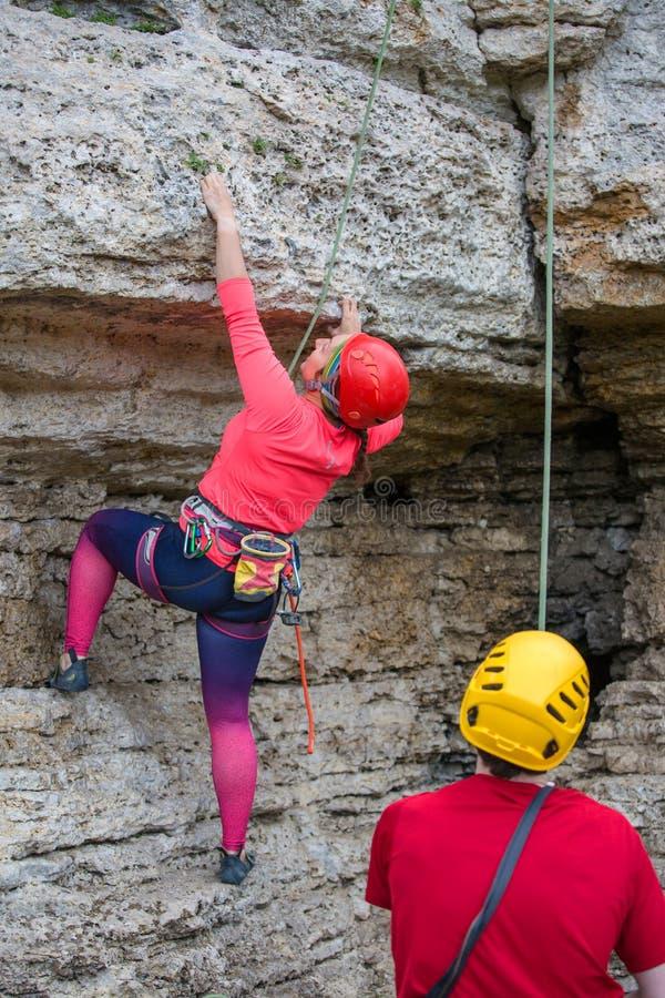 Foto von der Rückseite der Frau im Sturzhelm, der auf Berg und Männern mit Seil klettert lizenzfreie stockbilder