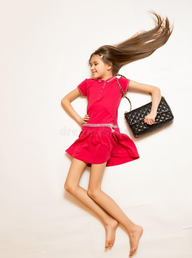 Foto von der Spitze des netten Mädchens mit dem langen Haar, das auf weißem Boden liegt stockfotos