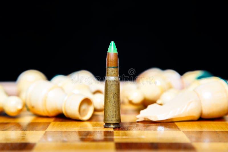 Foto von einer Kugel, die auf Schachbrett unter Lügenschachfiguren steht stockfotografie