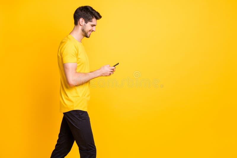 Foto von fröhlichem trendy positivem attraktiven Mann, der süchtig ist, durch sein Profil in den sozialen Medien zu blättern stockfotos