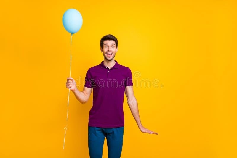 Foto von fröhlichen positiven beißenden Mann mit Luftkugel Helium mit Händen Hosenhose blau stockfotos