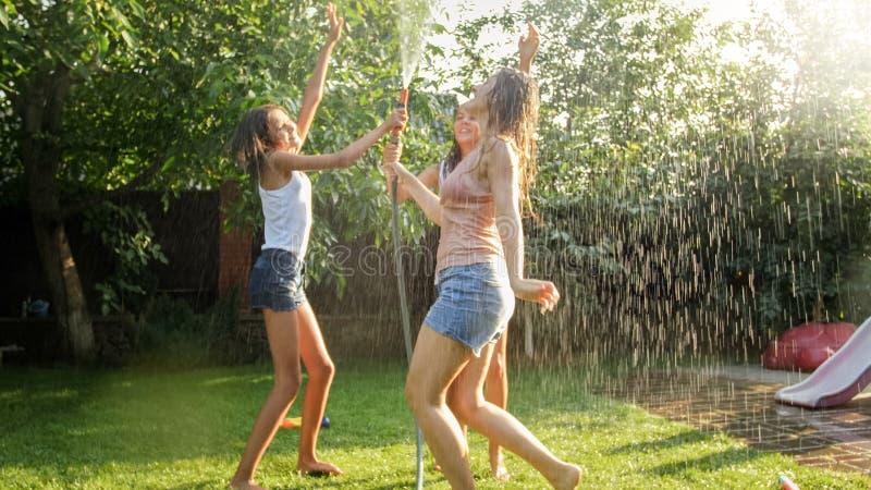 Foto von gl?cklichen netten M?dchen in der nass Kleidung, die unter Wassergartenschlauch tanzt und springt Familie, die Spa? spie stockfotografie