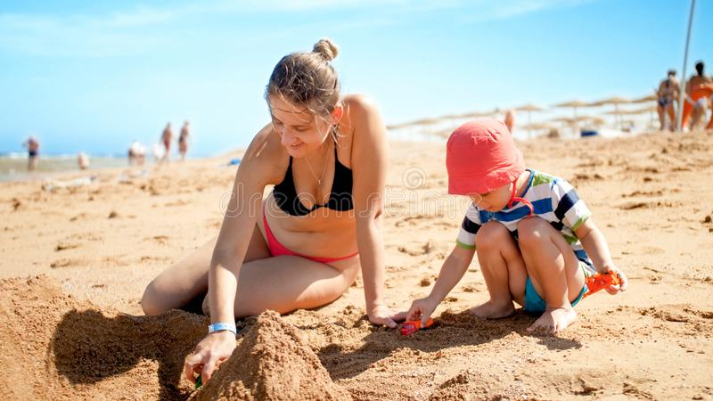 Foto von 3 Jahren alten Kleinkindjungengebäude-Sandburg mit junger Mutter der Ozeanstrand Familie, die Spaß sich entspannt und ha lizenzfreies stockbild