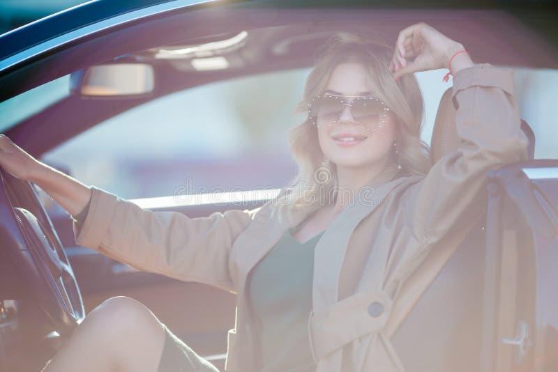 Foto von jungen Blondinen mit den Gläsern und langem Kleid, die im Auto mit offener Tür sitzen stockbild