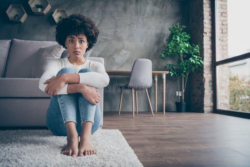 Foto von ziemlich dunkler Haut lockig Dame sitzend Fußboden in der Nähe von Sofa traurige Augen voller Angst halten Knie in der N lizenzfreies stockbild