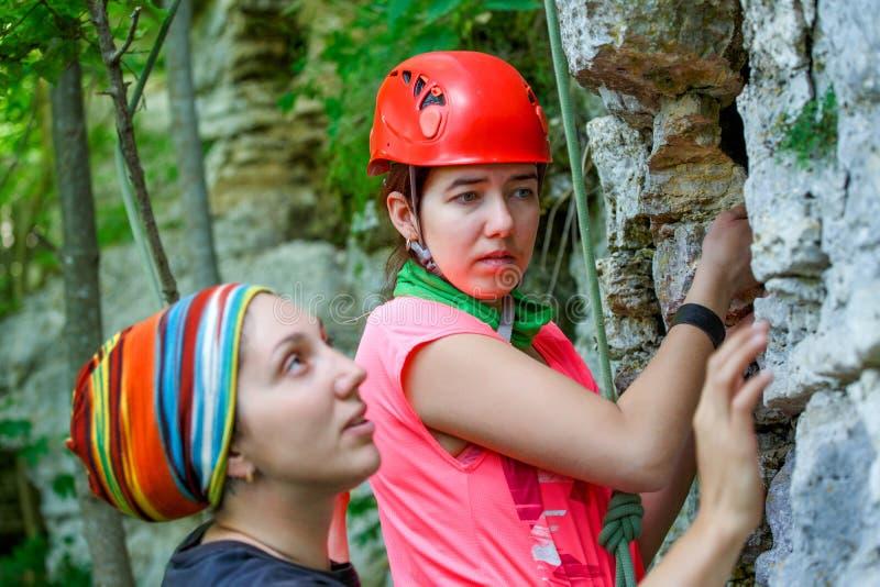 Foto von zwei Sportfrauen, die oben Berg klettern stockfoto
