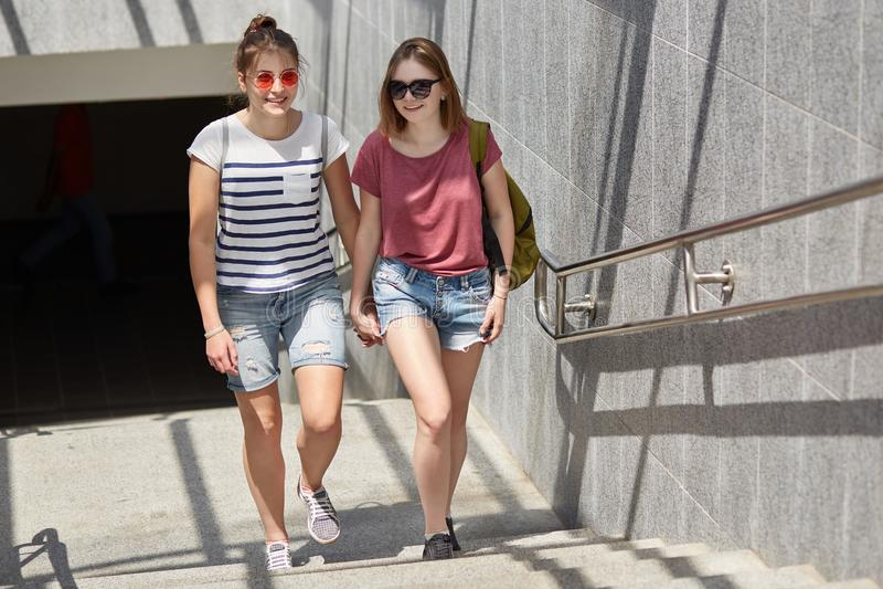 Foto von zwei weiblichen Lesben halten Hände, haben Weg in der Stadt, stehen nahe U-Bahn, trägt zufällige T-Shirts und Baumwollst lizenzfreie stockfotos