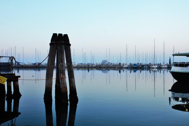 Foto, welches das Küstenpanorama der venetianischen Stadt Chioggia darstellt entlang dem Pier bei Sonnenuntergang lizenzfreie stockbilder