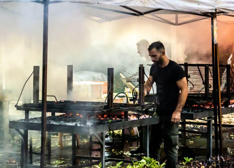 Foto, welches die Leute machen ein gegrilltes Fleisch untergetaucht im Rauche darstellt Feuer und Kohlen lizenzfreie stockfotos