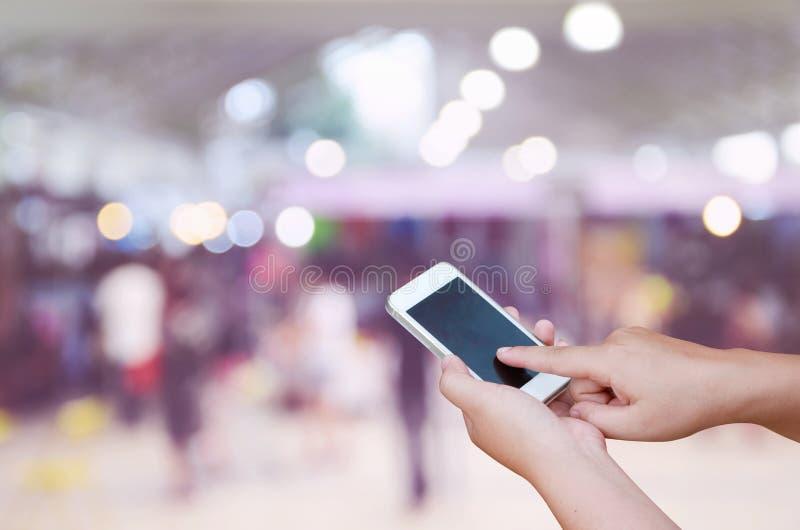 Foto y smartphone borrosos en feria profesional y una compras de parada fotos de archivo libres de regalías