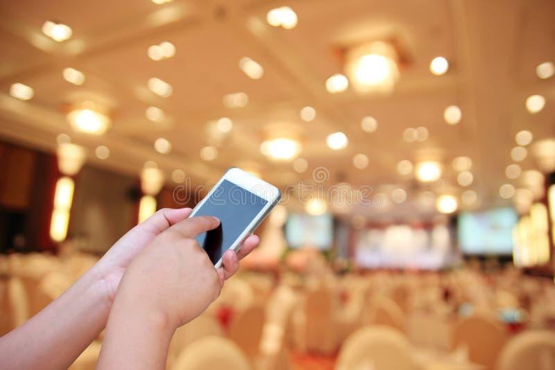 Foto y smartphone borrosos en sala de conferencias o sala de seminarios foto de archivo libre de regalías