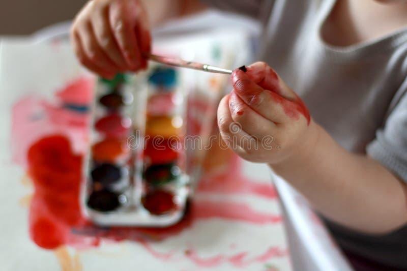 Fotobarnet trycker på borsten med smutsiga händer i målarfärgen mot en vattenfärgmålarfärgbakgrund royaltyfri foto