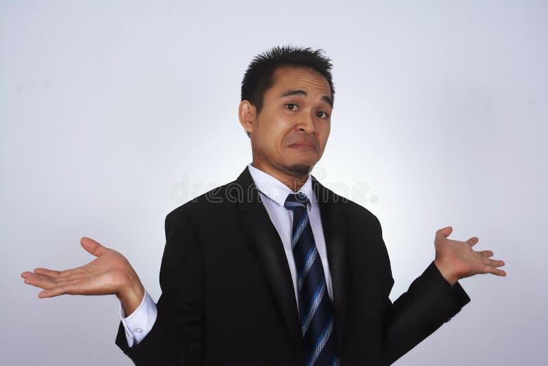 Fotobeeld van een knappe aantrekkelijke jonge Aziatische zakenman met trek ik ` t ken aan gebaar stock afbeelding