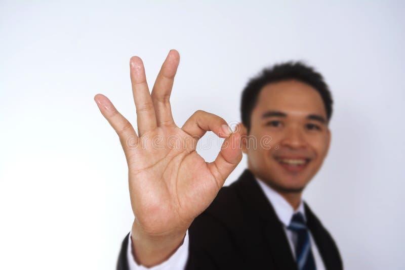 Fotobild av en stilig attraktiv ung asiatisk affärsman med den ok teckenhanden royaltyfri fotografi