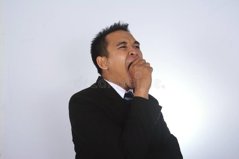 Fotobild av en stilig attraktiv ung asiatisk affärsman som gäspar gest royaltyfria bilder