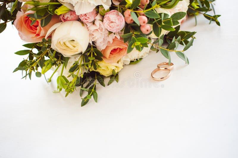 Fotobild av guld- cirklar för ett klassiskt bröllop av bruden och brudgummen på en vit tabell royaltyfria bilder