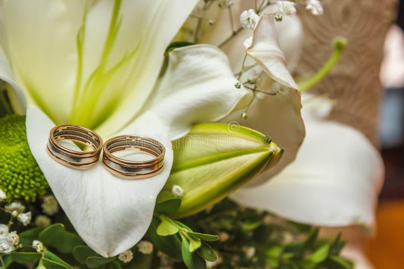 Fotobild av guld- cirklar för ett klassiskt bröllop av bruden och brudgummen på en vit tabell, med en härlig bröllopbukett av arkivbild