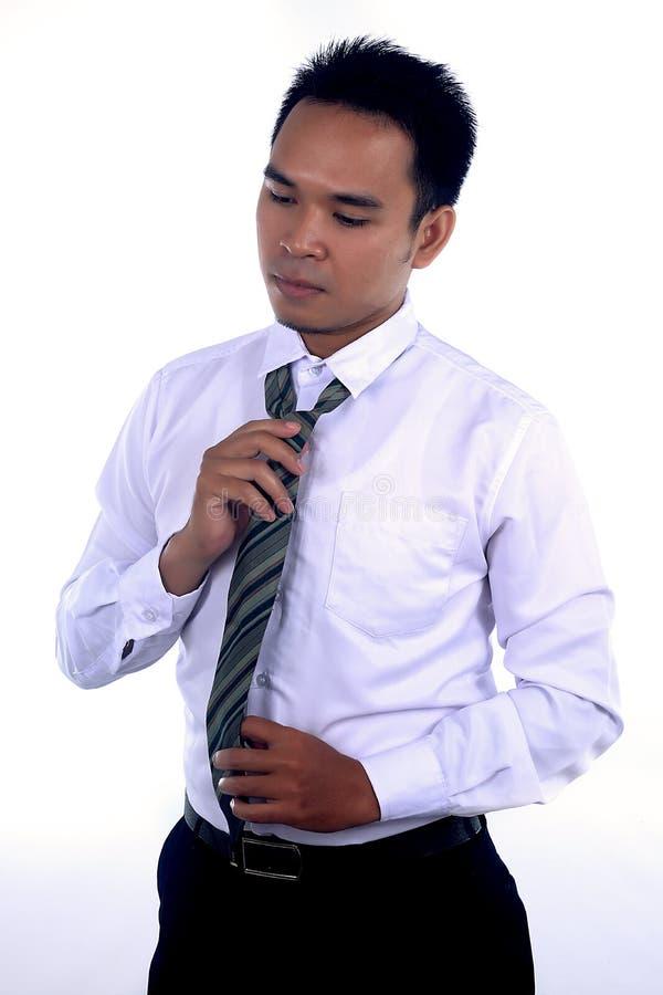 Fotobilden av en stilig attraktiv ung asiatisk affärsmandressing, fixande hans band och ordnar till för att arbeta royaltyfri fotografi