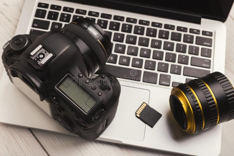 Fotocamera, lens en geheugenkaart op computer stock afbeelding