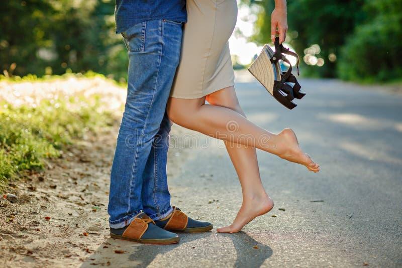 Fotoclose-up van voeten in schoenenmeisje en een kerel in laarzen op backg stock foto