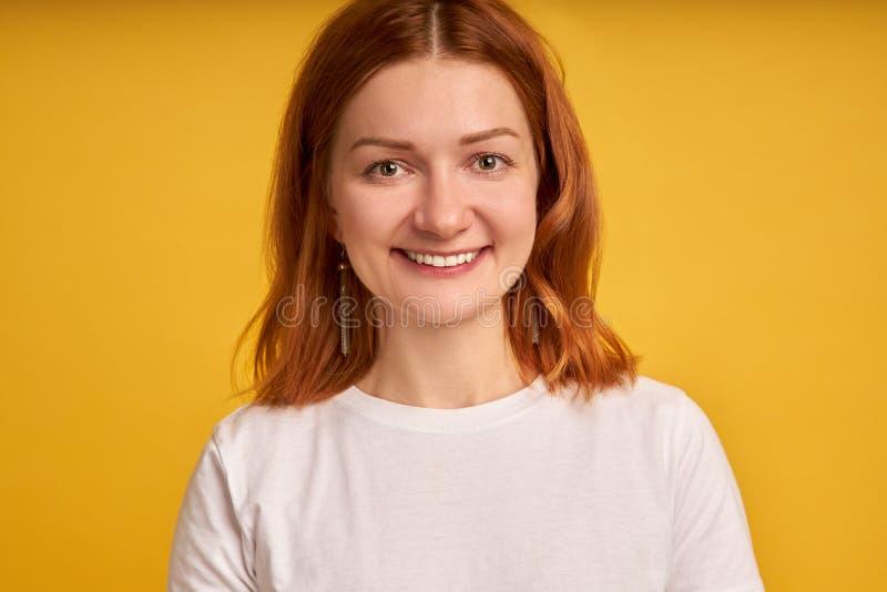 Fotocloseup av den optimistiska kvinna20-tal med lockigt ljust rödbrun hår som ler på kameran som isoleras över gul bakgrund royaltyfri foto