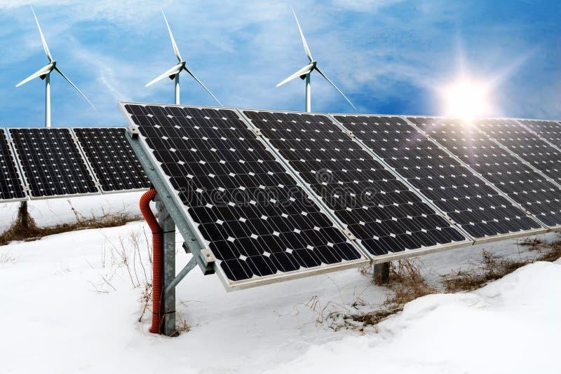 Fotocollage av solpaneler och vindturbins i vinter med snö arkivbilder