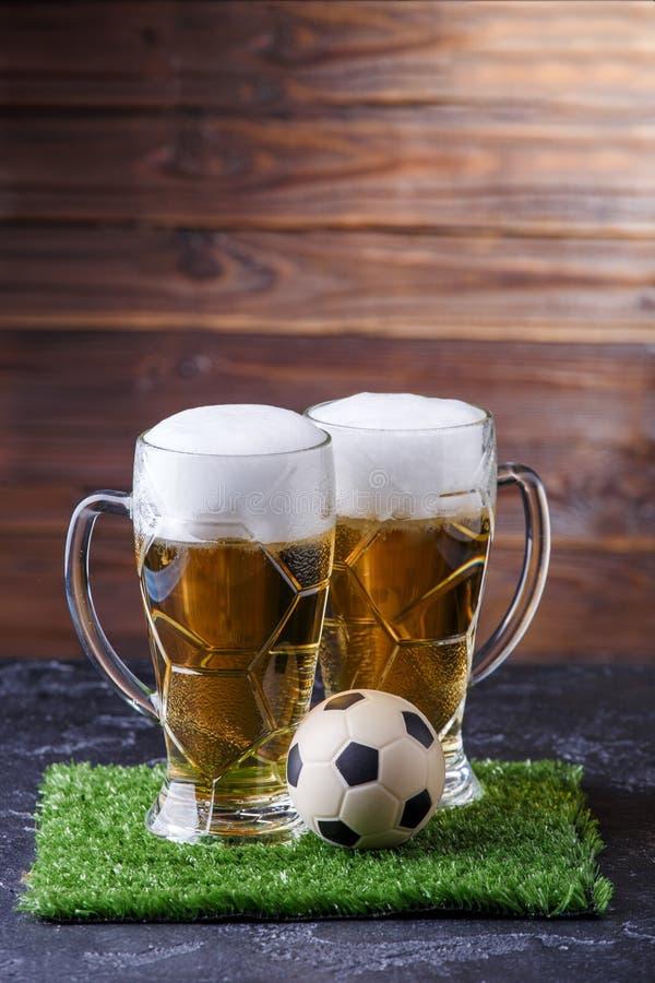 Fotoet av öl två rånar, grönt gräs med fotbollbollen arkivfoto