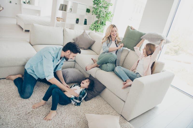 Fotoet av adoptiv- medlemmar för familj fyra spenderar fritid som jublar fniss för kuddekamp, sitter soffavardagsrum fotografering för bildbyråer