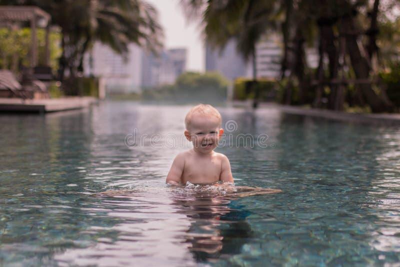 Fotoet av aktiv behandla som ett barn simning i pöl i Bangkok arkivbilder